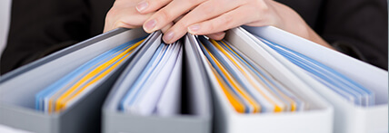 Close-up image of a businesswoman leaning against four grey and white binder folders.