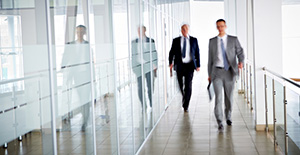 A businessman in a grey suit, followed by an older businessman in a black suit, walk briskly through a brightly-lit office hallway.