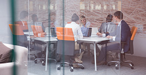 Shot of a team of colleagues working together at a white conference table, sitting in grey and orange chairs, as seen through a glass divider.