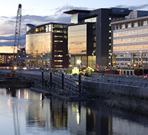 A set of modern, multi-story office buildings on the banks of the Clyde river in Glasgow city centre, as shot as dusk.