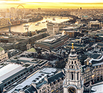A birds eye view of central London at sunrise, with the Thames and London Eye visible in the background.