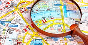 A large, wooden magnifying glass sits on top of a road map of the City of London, highlighting the Thames and Waterloo Road.