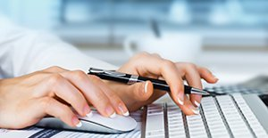 Close up of female hands typing on a laptop and using a mouse