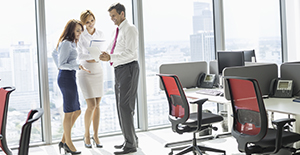A businessman shows a file to two of his female colleagues as they stand in a workspace on a high floor in a tall, modern office building.