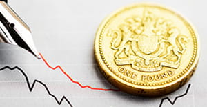 A one pound coin sits on top of a piece of graph paper, where an ink pen has drawn two bumpy lines.