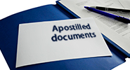 Close-up image of a bound, blue document with an envelope sitting on top that reads: 'Apostilled documents'.