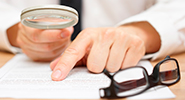 Close-up image of a businessman holding a magnifying glass to a document, pointing to a line next to his glasses