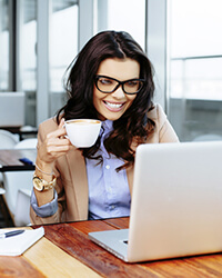 A businesswoman wearing a tan jacket and large, black glasses smiles at her laptop computer as she holds a white cup of coffee.
